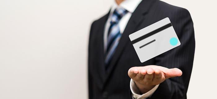 クレジットカードを手に浮かべる男性